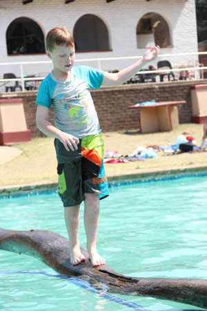 Kid on pole in pool